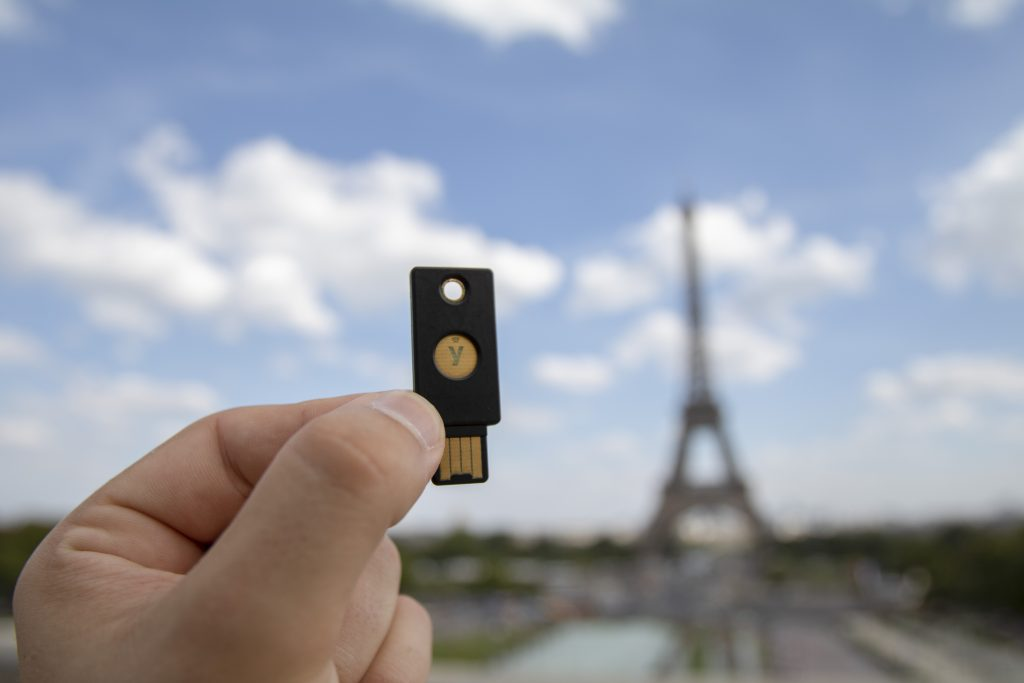 hand holding YubiKey with eiffel tower in background