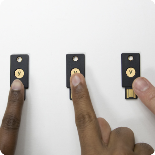 Fingers touching YubiKeys