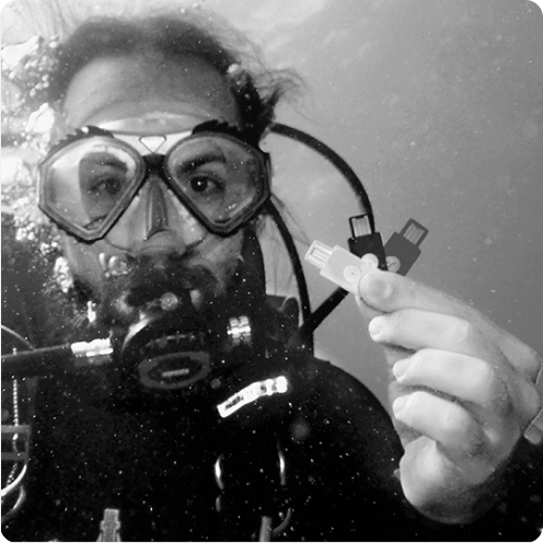 Scuba diver holding three YubiKeys under water
